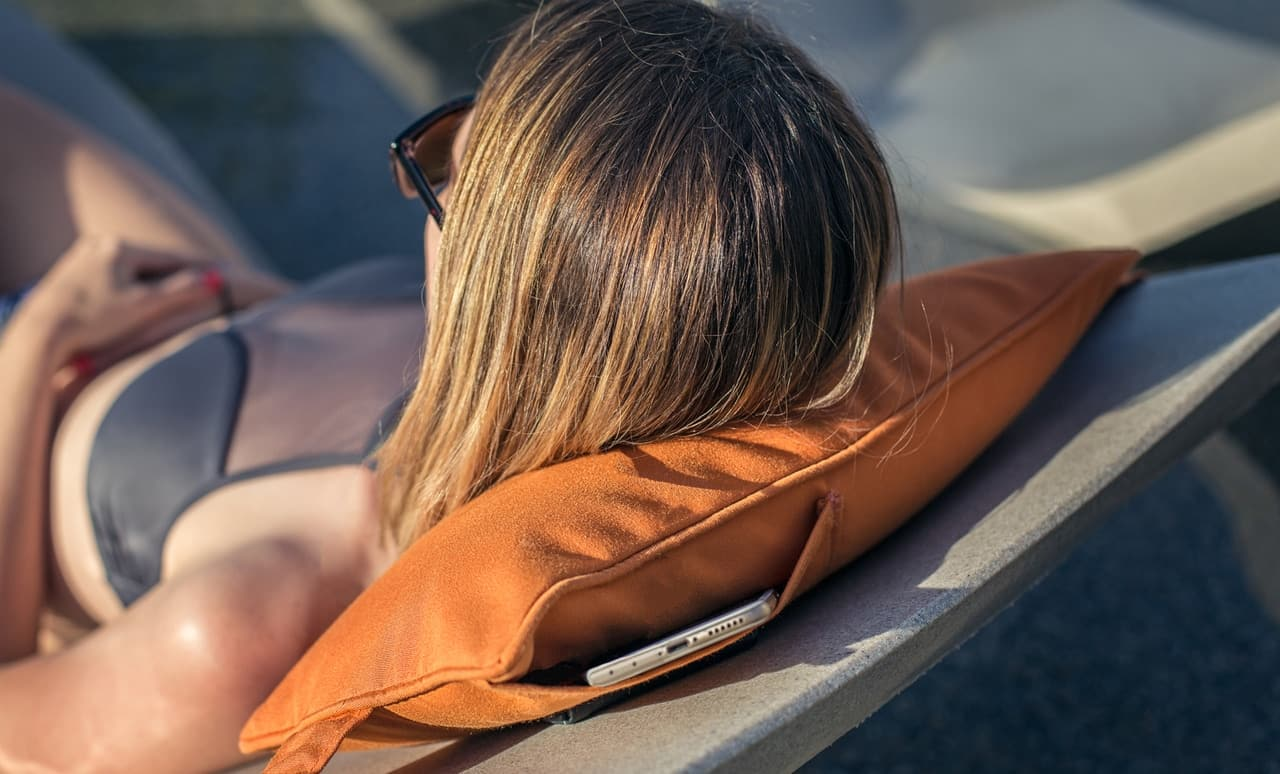Woman lounging comfortably with the Signature Headrest Pillow.
