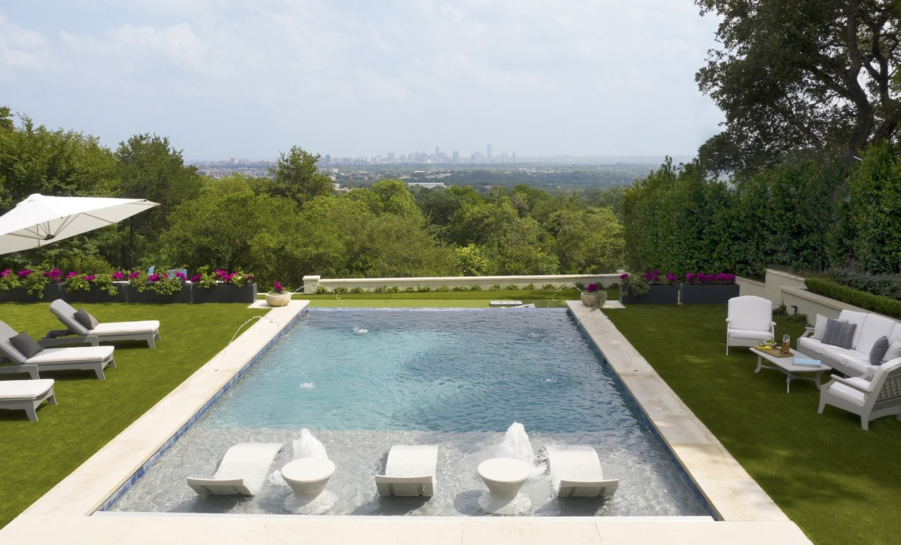 Outdoor pool scape with a variety of Ledge Lounger in pool at outdoor furniture including the Signature Chaise.