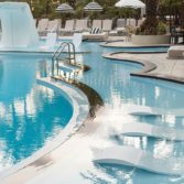 Ledge Lounger Signature Chaise in a public pool setting.