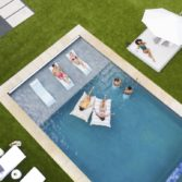 Arial view of a backyard pool with friends enjoying a variety of Ledge Lounger in pool furniture.