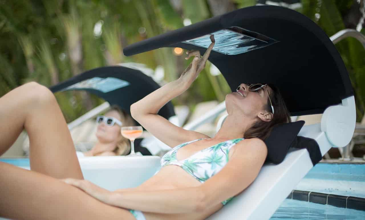 Woman enjoying a Ledge Lounger in the pool with the help of a Signature Headrest Pillow and shade.