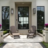 Legacy Adirondack chairs with matching ottomans on a porch.
