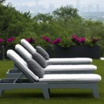A trio of Legacy Chaise Loungers in a manicured yard.
