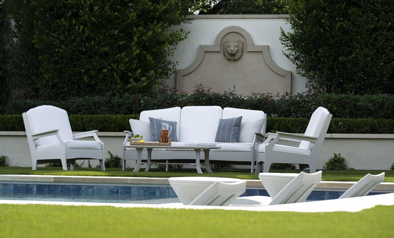 Beautiful pool side seating area near a pool with Ledge Lounger furniture.