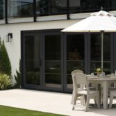 Outdoor space with Ledge Lounger dining table, chairs and umbrella.