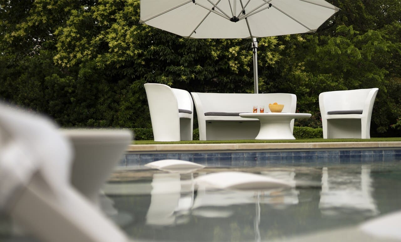 An Affinity oval outdoor coffee table surrounded by chairs poolside.