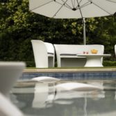 Affinity chairs, loveseat and oval outdoor coffee table overlooking a backyard pool.