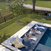 Ledge Lounger in pool furniture being enjoyed by friends.