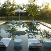 A pool set up with an assortment of Ledge Lounger in pool furniture.