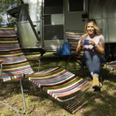 Woman enjoys a drink sitting in a Playnk chair by Ledge Lounger.