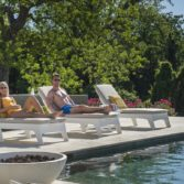 Couple lounging next to a pool ledge.