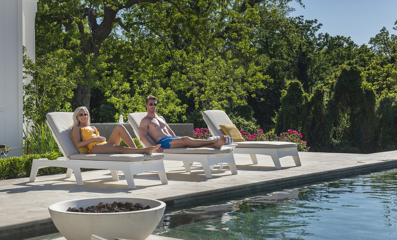 Couple enjoying Mainstay Chaise loungers poolside.