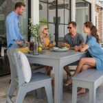 Friends chatting while sitting around a Ledge Lounger patio dining table.