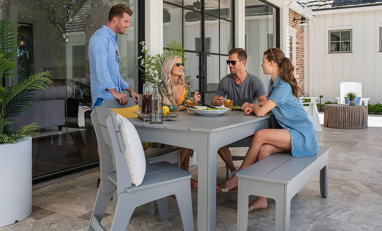 Friends gathered around Ledge Loungers outdoor dining table.