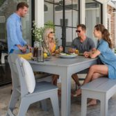 Friends gathering around a Ledge Lounger outdoor patio dining table.
