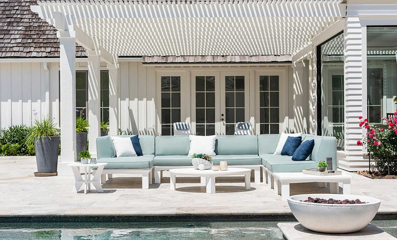Mainstay sectional with cushions and pillows overlooking a beautiful backyard pool.