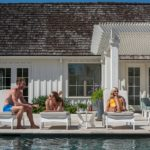 Friends chatting poolside on Ledge Loungers outdoor furniture.