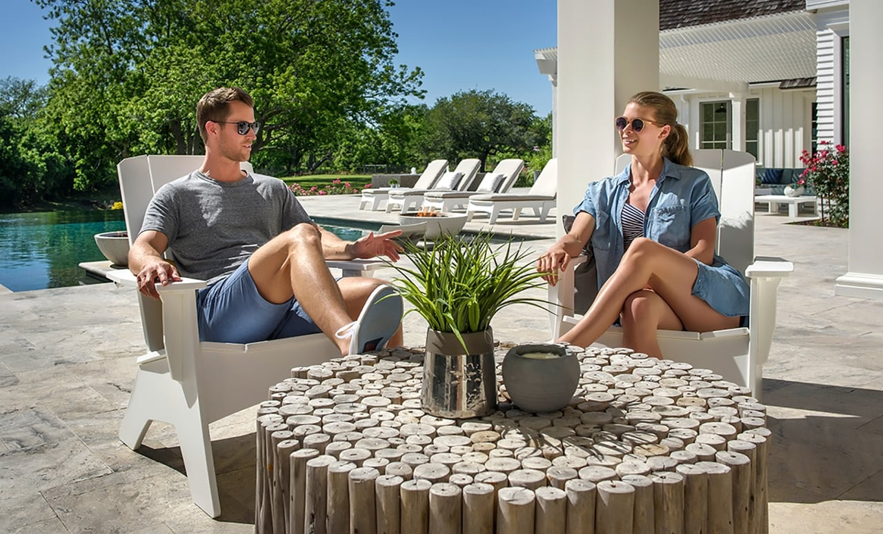 A couple enjoying their patio and sunshine in a pair of Ledge Lounger Adirondack chairs.