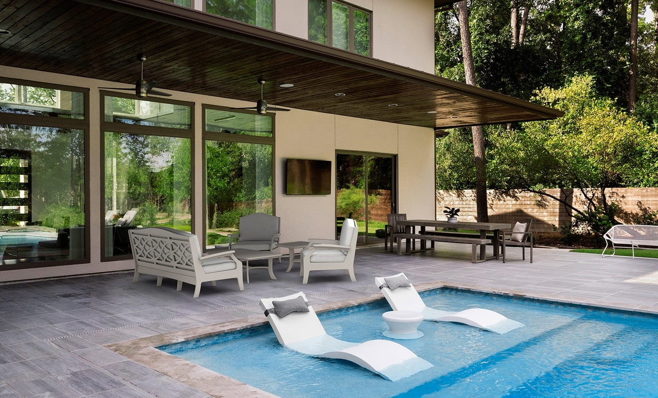 Beautiful outdoor space with Ledge Lounger in pool and patio furniture.