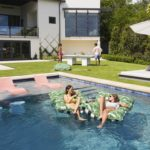 Group of friends enjoying Ledge Lounger in pool products and backyard games.