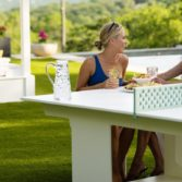 Women chatting poolside in Playnk dining chairs at the multi purpose ping pong table.