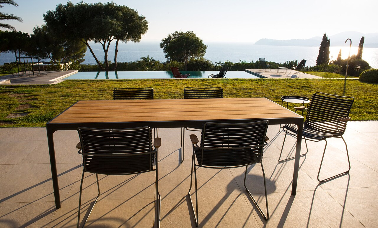 Playnk Dining Armchair's and table overlooking a beautiful pool.