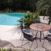 The Playnk Round Dining Table and matching chairs near a pool.