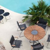 The Playnk Round Dining Table and chairs near a pool.