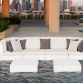 Ledge Lounger in pool sectional sofa on a pool ledge overlooking a city.