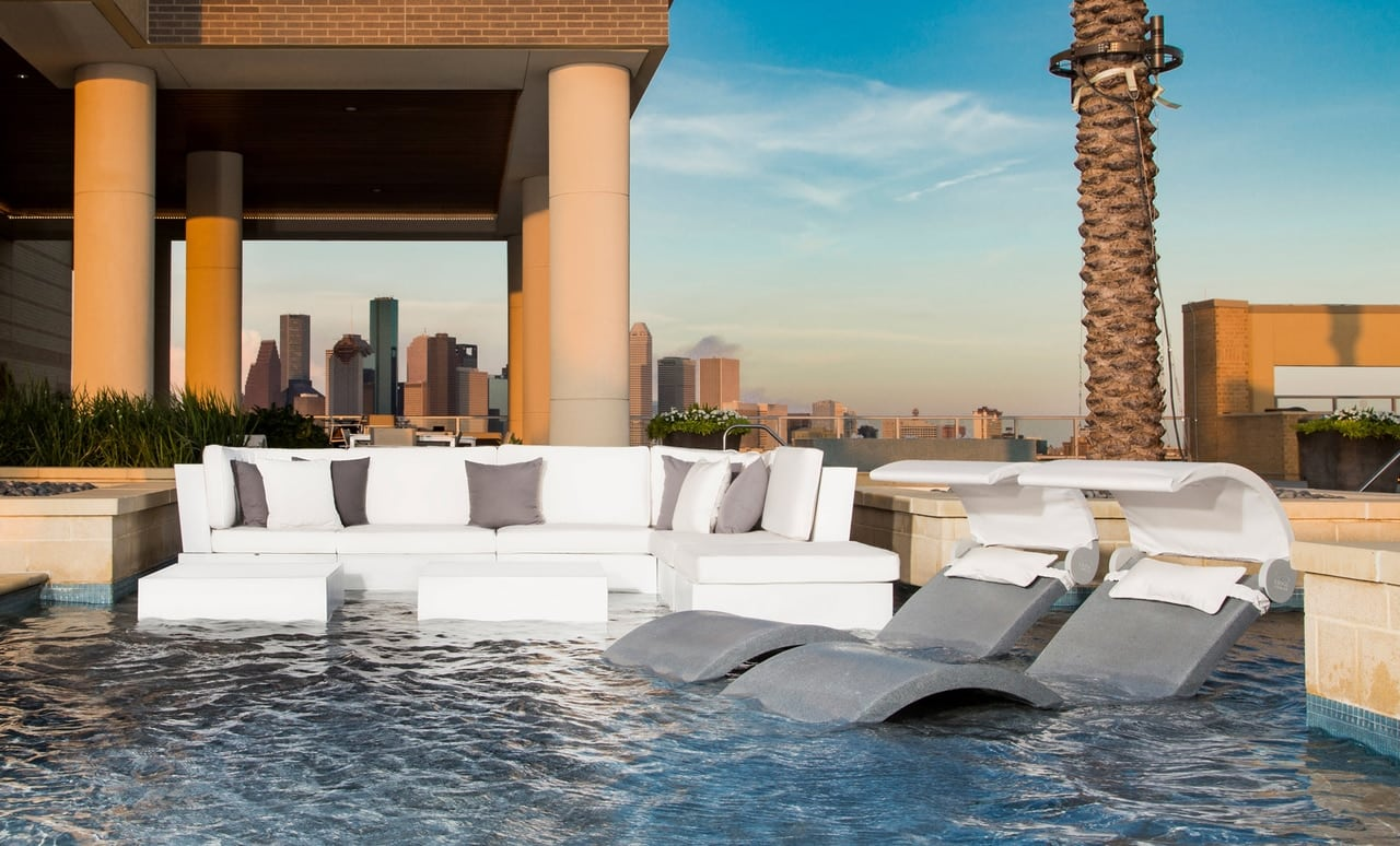 Ledge Loungers in pool sectional and Signature Chaise on a pool ledge overlooking a city.