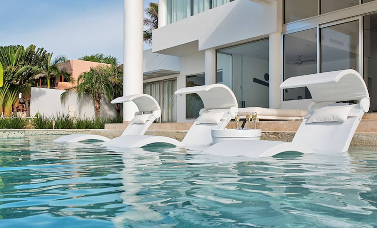 Pool scape with three Signature Chaise Deep chairs with headrests and shades.