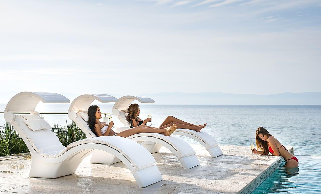 Friends enjoying Ledge Lounger Signature chairs oceanside.