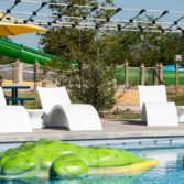 Several Ledge Lounger Signature Chaise Deep chairs overlooking a pool.