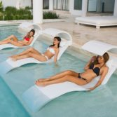 Three friends enjoying their in pool chaise's with shades from Ledge Lounger.