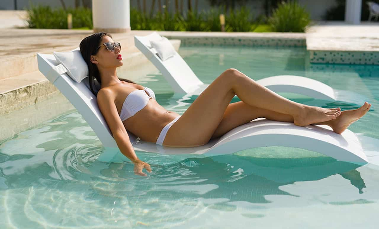 Woman enjoying a Signature Chaise Deep on a pool sun shelf.