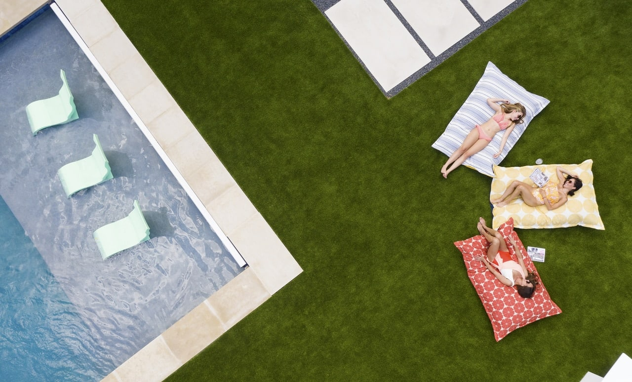 Friends soaking up the sun while laying on Laze Pillows near the pool.