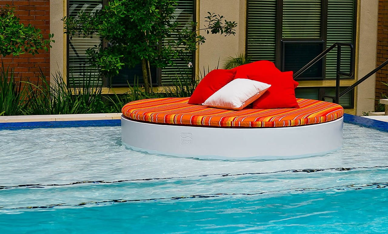 The Ledge Lounger Signature Round Sunbed with colorful cushion and pillows.