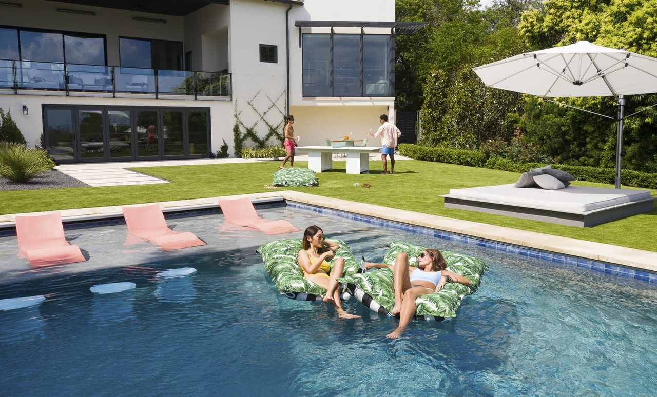 Friends enjoying Laze Pillows in a backyard pool.