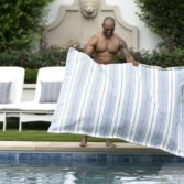 Homeowner putting his Laze Pillow in the pool.