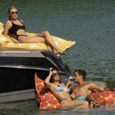 Adults enjoying laze pillows near a boat on a lake.