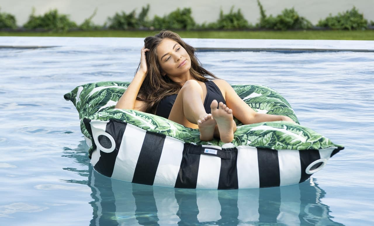 Woman enjoying relaxing on a Laze Pillow in her pool.