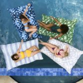 Group of friends enjoying Laze Pillows in the pool.