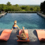 Friends enjoying coral colored Signature Chaise on the pool ledge.