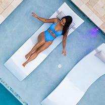 woman on a ledge lounger in pool chaise